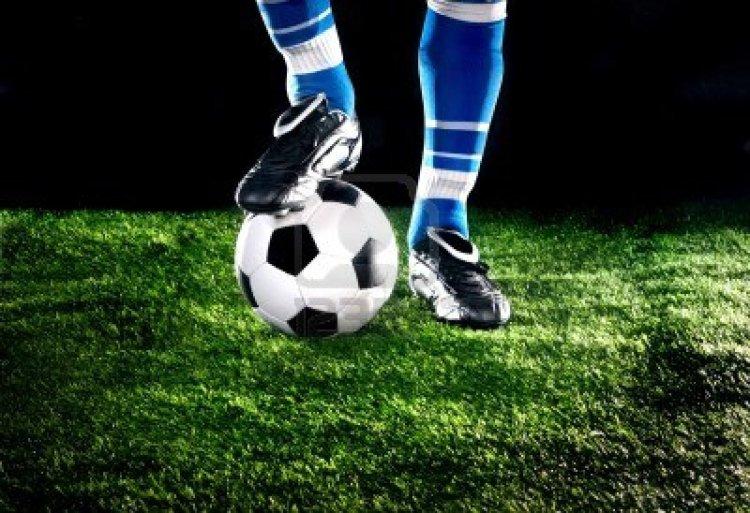 11010829-balon-de-futbol-con-los-pies-en-el-campo-de-futbol